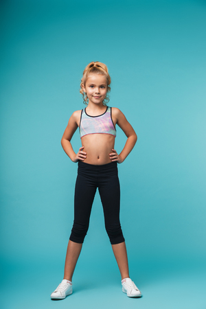 Image of a cute little girl child make fitness exercises isolated over blue wall. Archivio Fotografico