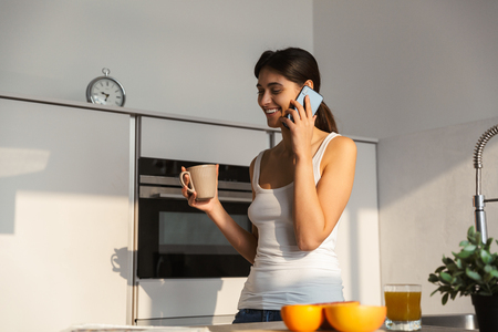Pretty young girl standing at the kitchen in the morning, having cup of coffee, talking on mobile phone