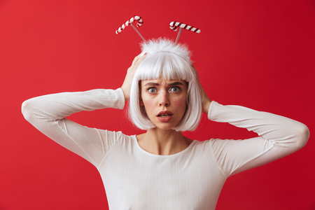Image of a scared young woman wearing christmas carnival costume over red wall. Stock Photo