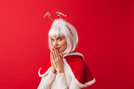 Beautiful young girl wearing red Christmas costume standing isolated over red background, begging