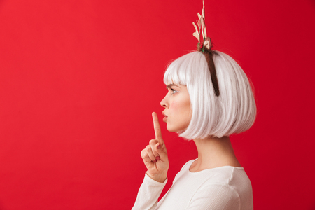 Image of a cute woman isolated over red wall background wearing deer ears costume carnival showing silence gesture.