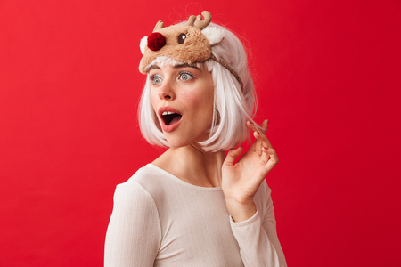 Image of an excited young shocked woman dressed in carnival christmas costume posing isolated over red wall background.