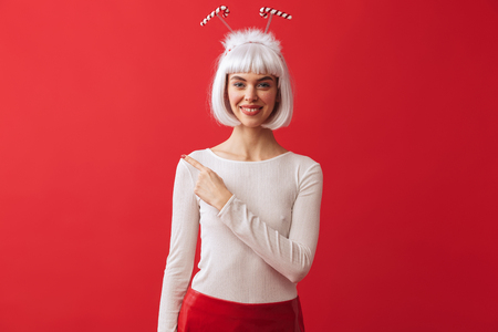 Image of a happy young woman wearing christmas carnival costume over red wall pointing.