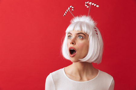 Image of a shocked excited young woman wearing christmas carnival costume over red wall. Stock Photo