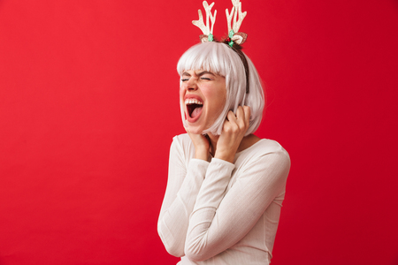 Pretty young girl wearing Christmas deer horns standing isolated over red background 版權商用圖片