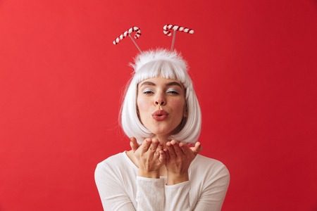 Image of a cute young woman wearing christmas carnival costume over red wall blowing kisses.