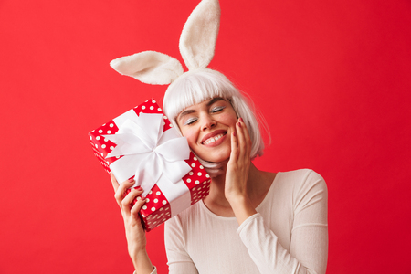 Cheerful young girl wearing Christmas bunny ears standing isolated over red background, holding gift box