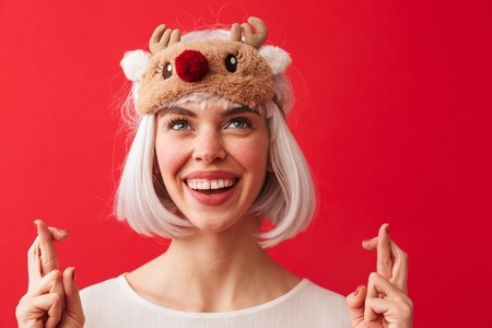 Image of a young happy woman dressed in carnival christmas costume posing isolated over red wall background showing hopeful gesture.