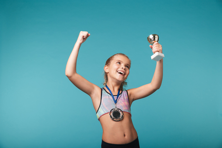 Cheerful little sports girl celebrating the win isolated over blue background, wearing a gold medal, showing a trophy