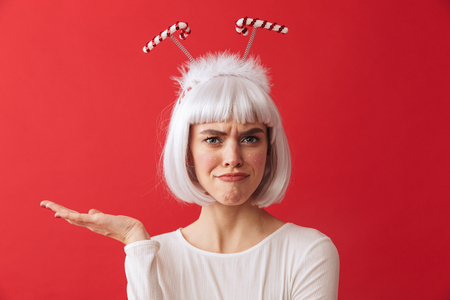 Image of a confused young woman wearing christmas carnival costume over red wall.