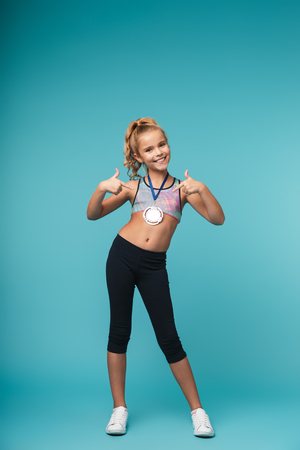 Cheerful little sports girl celebrating the win isolated over blue background, wearing a gold medal