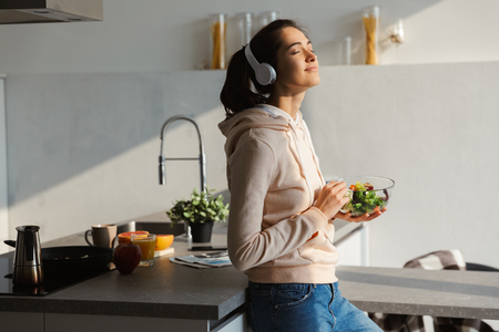 Image of an amazing happy healthy woman in the kitchen standing daily morning routine eat salad listening music in headphones.