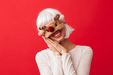 Pretty young girl wearing Christmas deer mask standing isolated over red background, arms folded at her face