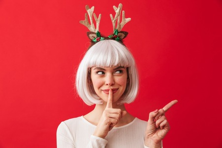 Image of a cute woman isolated over red wall background wearing deer ears costume carnival showing silence gesture pointing.