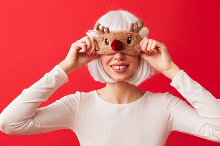 Pretty young girl wearing Christmas deer mask on her face standing isolated over red background 写真素材