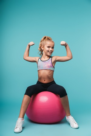 Cheerful little girl wearing sport clothes doing exercises with fitness ball isolated over blue background Stock Photo - 116054376