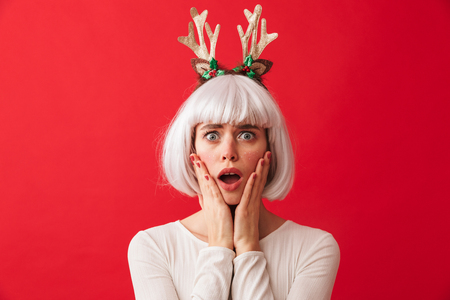 Pretty young girl wearing Christmas deer horns standing isolated over red background 写真素材