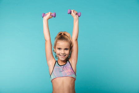 Smiling little sports girl doing exercises with dumbbells isolated over blue background Foto de archivo