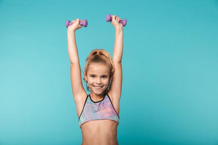 Sonriente niña deportiva haciendo ejercicios con pesas aislado sobre fondo azul. Foto de archivo