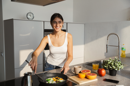 Image of an amazing happy healthy woman in the kitchen standing daily morning routine cooking breakfast.