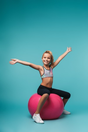 Cheerful little sports girl sitting on a fitness ball isolated over blue background Stock Photo