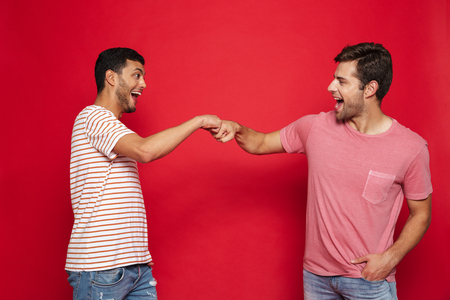 Two cheerful young men standing isolated over red background, giving fist bump
