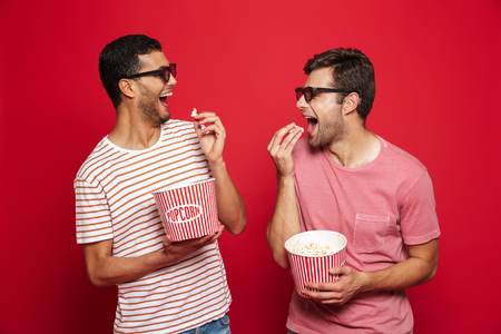 Two cheerful young men standing isolated over red background, eating popcorn, wearing 3d glasses
