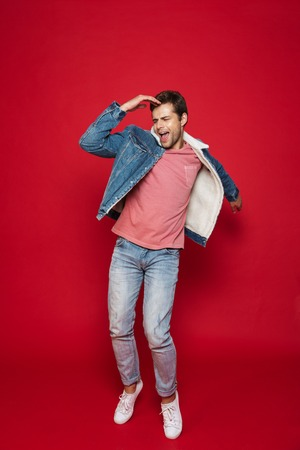 Full length of a happy young man wearing warm denim jacket jumping isolated over red background Reklamní fotografie
