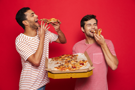 Image of a handsome pleased happy young men friends isolated over red wall background holding big pizza eating. 免版税图像