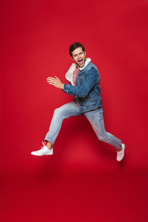 Full length of a happy young man wearing warm denim jacket jumping isolated over red background 스톡 콘텐츠