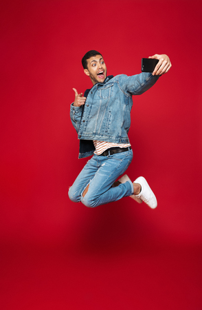 Full length of a cheerful young man wearing warm denim jacket jumping isolated over red background, taking a selfie