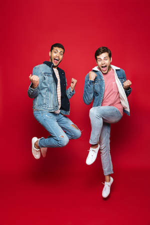 Full length of two cheerful young men jumping isolated over red background, celebrating success