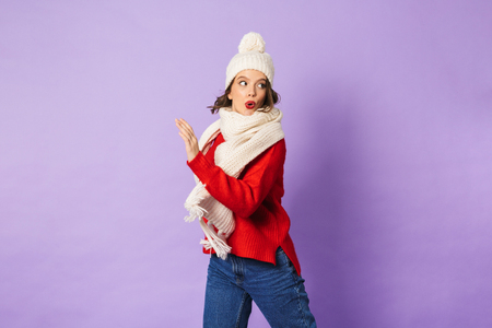 Portrait of a shocked young woman wearing winter hat isolated over purple background.