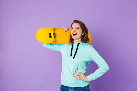 Image of an amazing happy young woman posing isolated over purple background wall holding skateboard.