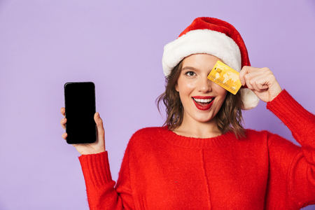 Portrait of a happy young woman wearing christmas hat isolated over purple background using mobile phone holding credit card. Stockfoto