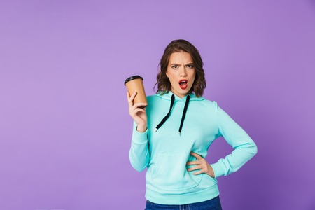 Picture of an displeased beautiful young woman posing isolated over purple background wall drinking coffee.
