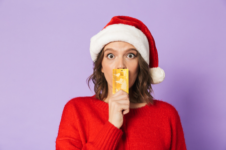 Image of an excited shocked young woman wearing christmas hat isolated over purple background holding debit card. Stock Photo