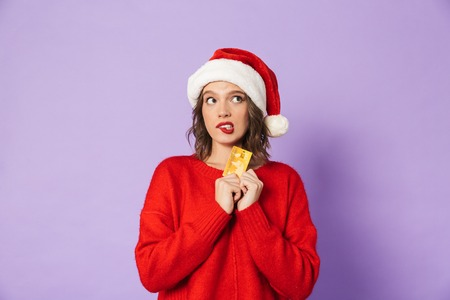 Portrait of an excited happy young woman wearing christmas hat isolated over purple background holding debit card bite lip. Stock Photo