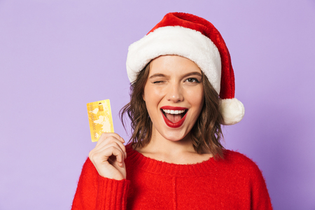 Portrait of an excited happy young woman wearing christmas hat isolated over purple background holding debit card winking.