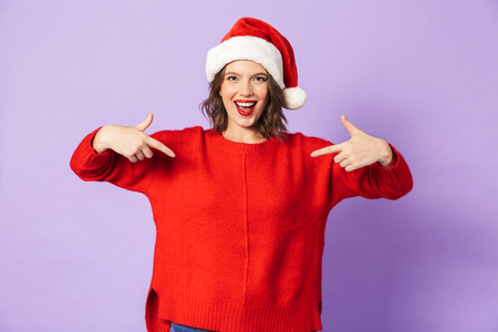 Portrait of an excited happy young woman wearing christmas hat isolated over purple background pointing. Stock Photo