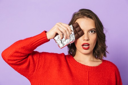 Image of a shocked emotional young woman posing isolated over purple background wall covering eye with chocolate.