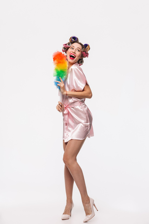 Full length portrait of a pretty housewife with curlers in her hair wearing robe standing isolated over white background, posing with a duster Stock Photo