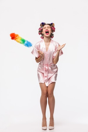 Full length portrait of a pretty angry housewife with curlers in her hair wearing robe standing isolated over white background, posing with a duster