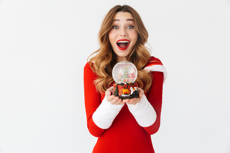 Portrait of cheerful woman 20s wearing Santa Claus red costume smiling and holding Christmas snow ball isolated over white background Stock Photo