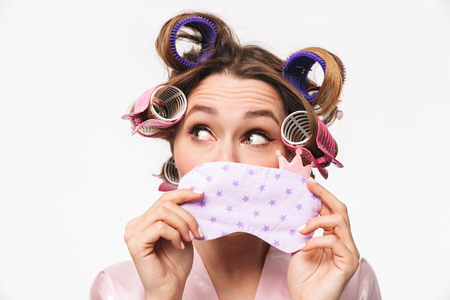 Pretty housewife with curlers in hair wearing robe isolated over white background, holding sleep mask Banco de Imagens