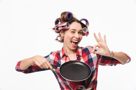 Happy housewife with curlers in hair standing isolated over white background, holding frying pan, showing ok