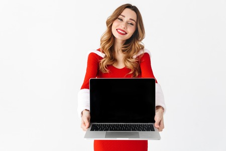 Image of a pretty excited woman in christmas costume showing display of laptop computer.