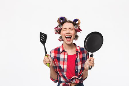 Wütende Hausfrau mit Lockenwicklern im Haar, die isoliert auf weißem Hintergrund steht und eine Bratpfanne hält