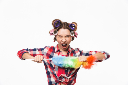 Angry housewife with curlers in hair standing isolated over white background, holding duster