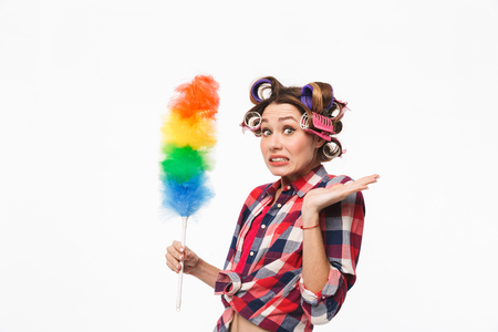 Busy housewife with curlers in hair standing isolated over white background, holding duster